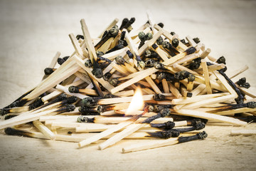 Burnt matches stack with burning match on wood
