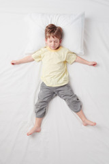 Top view of little boy sleeping in Star pose