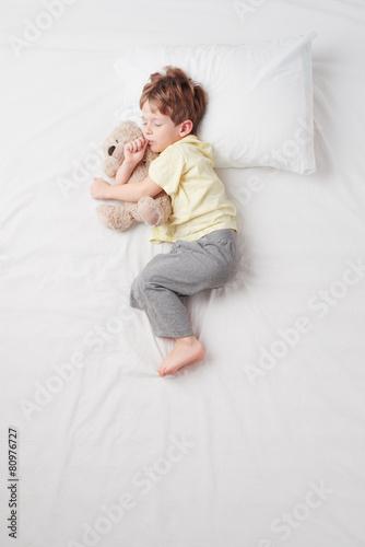 Leinwandbild Motiv Top view of little boy sleeping in Foetus pose