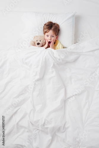Top view of little scared by nightmares boy under blanket - 80976757