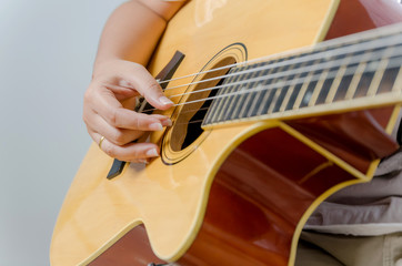 Female hand playing music by acoustic guitar - Close up shot and