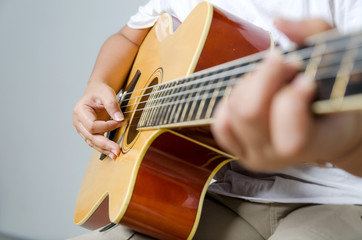 Female hand playing music by acoustic guitar