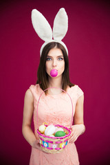 Woman in bunny ears holding Easter egg basket