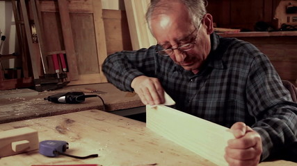 Senior carpenter carving wood with engraver tool.