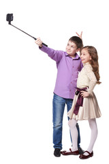 Boy and girl taking selfies with selfiestick on her smartphone