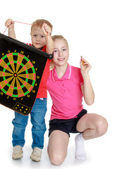 Brother and sister playing a game of darts.