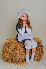 Girl in dress sitting on a rustic vintage straw bale.