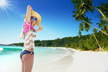 long haired blonde woman with flower in hair in bikini on