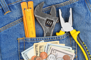 Earnings concept - money and tool in blue jeans pocket