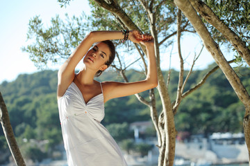 Beautiful girl in white dress holding branch of olive tree