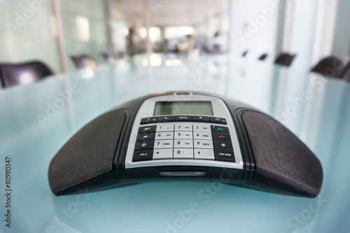 Inside modern conference room, focus on phone - 80980347