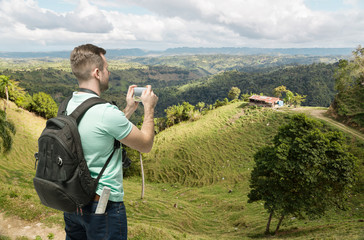 Tourist man taking photo of hills in Dominicana