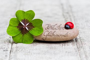 Glücksbringer mit Stein auf Holz, Herzlichen Glückwunsch