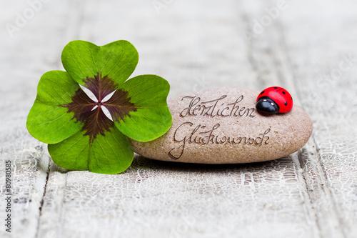 Leinwandbild Motiv Glücksbringer mit Stein auf Holz, Herzlichen Glückwunsch