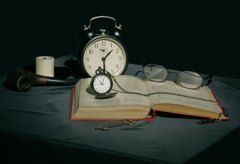 Still life with a book and clocks in dark colors