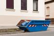 Leinwanddruck Bild - Ein blauer Container für Abfall steht vor einem Wohnhaus