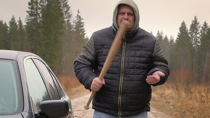 Aggressive man with a baseball bat near car