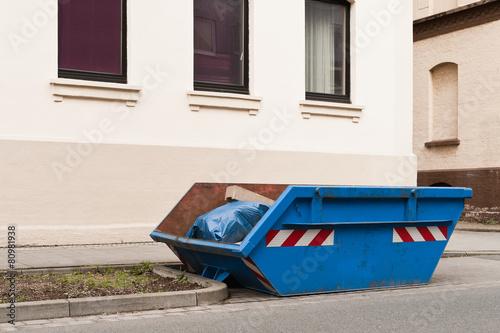 Leinwanddruck Bild Ein blauer Container für Abfall steht vor einem Wohnhaus