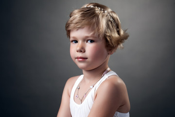 Portrait of pretty little girl posing in studio
