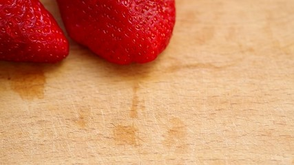 Laying red strawberries on a wooden table