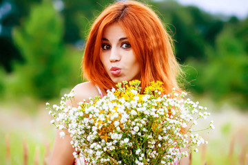 portrait of a young red-haired girl with wild flowers