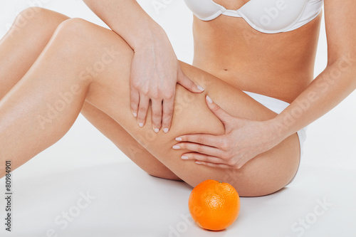 Beautiful female body with orange on a white background