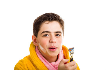 Smiling boy in yellow bathrobe and pink towel stares at the razo