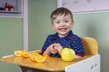 Happy toddler eating fruit