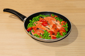 Aluminum Pan full of salmon steaks, peas, tomatoes and capers