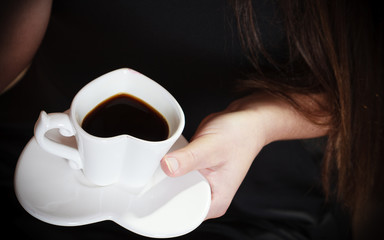 Female hand holds coffee cup