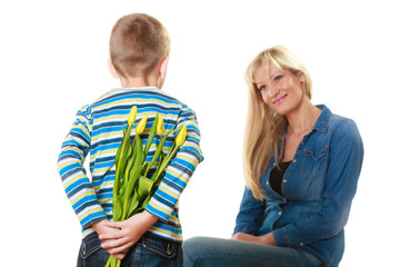 Child boy giving flowers his mother