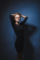 European appearance blonde girl with glasses in a black dress ho