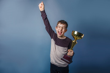 European-looking boy of ten years in glasses  holding  a cup  in