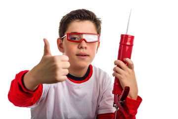Soft skinned Boy wearing red goggles and holding a caulking gun