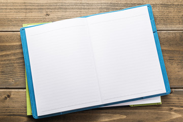 Empty notebook on wooden desk table.