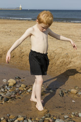 Young Boy playing in rock pool at seaside.