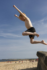 Young boy jumping from sea wall at seaside.