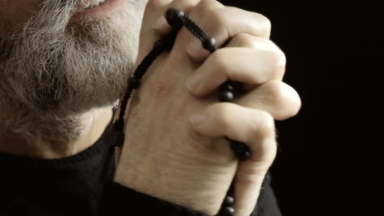 Religious man praying detail cross hands