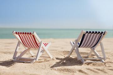 Two Deckchairs On Beach