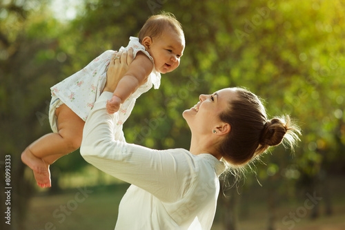 Mother Lifting Up And Turning Around Little Baby Daughter In Par - 80993333