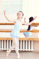 Artistic girl posing at camera in ballet class