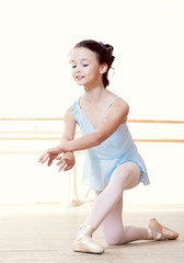 Little dancer doing exercises in ballet studio