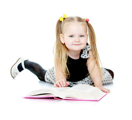 Adorable little girl with pigtails reading a book.