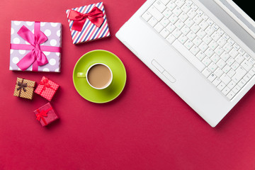 Cup of coffee and gift near computer