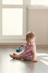 Little girl playing with pyramid on floor