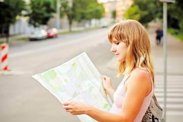 Young caucasian woman walking on the street and looking at map.