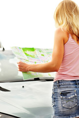 Young caucasian woman standing near a car and looking at map.