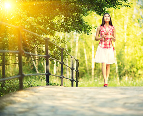 Young woman walking in spring park.