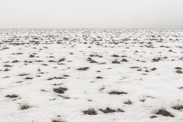 snow plowed field with thawed bumps in the fog