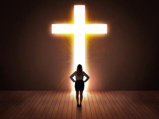 Woman looking at bright cross sign